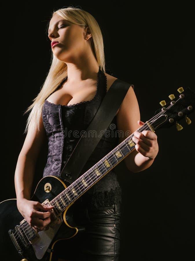 弹电吉他的性感的白肤金发的女性 免版税图库摄影