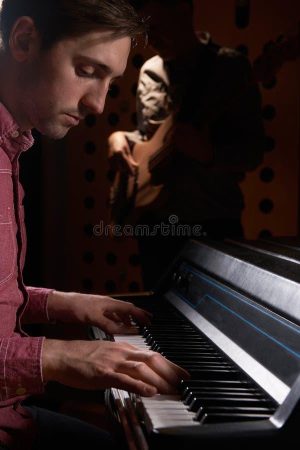 弹电钢琴和低音吉他在记录的音乐家St 免版税库存图片
