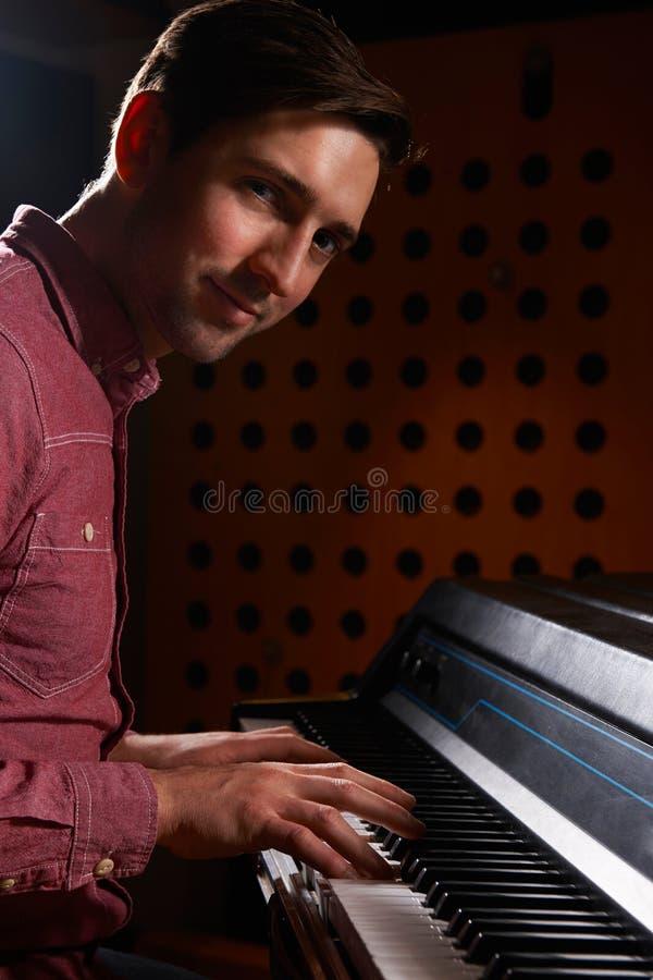 弹电钢琴的音乐家在录音室 库存照片