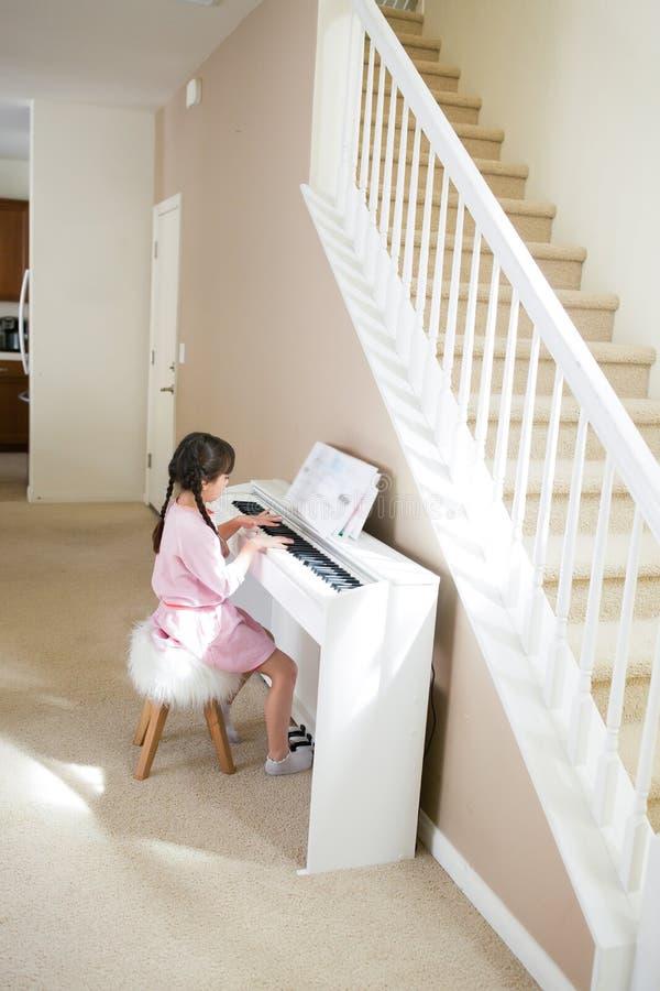 弹白色钢琴的女孩 免版税库存照片