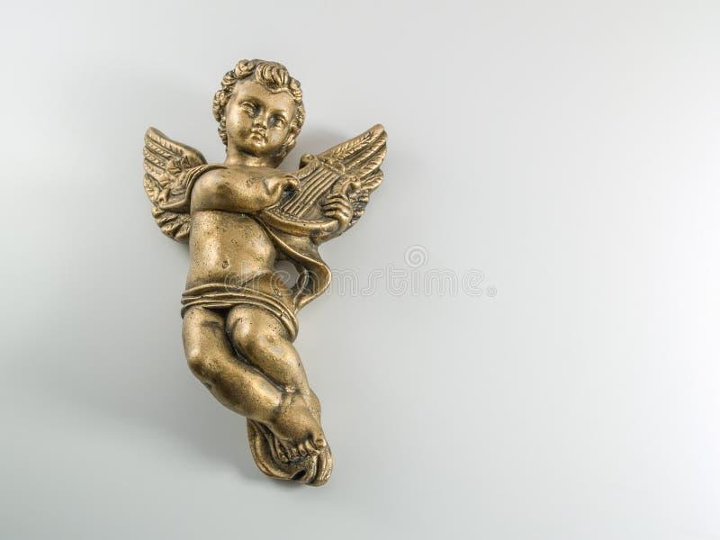 弹竖琴的金天使 免版税库存照片