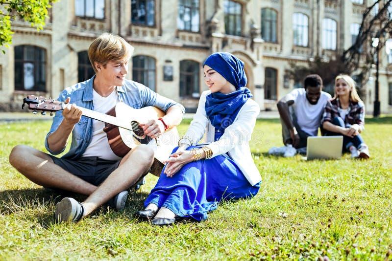 弹美丽的女孩的英俊的人吉他 库存照片