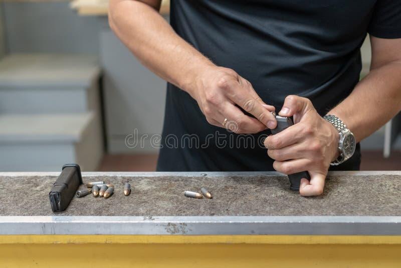 弹药筒 人的手充电枪与弹药 r 免版税库存照片