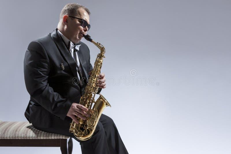 弹萨克斯管的太阳镜的成熟轻松和体贴的白种人萨克管演奏员 免版税库存照片