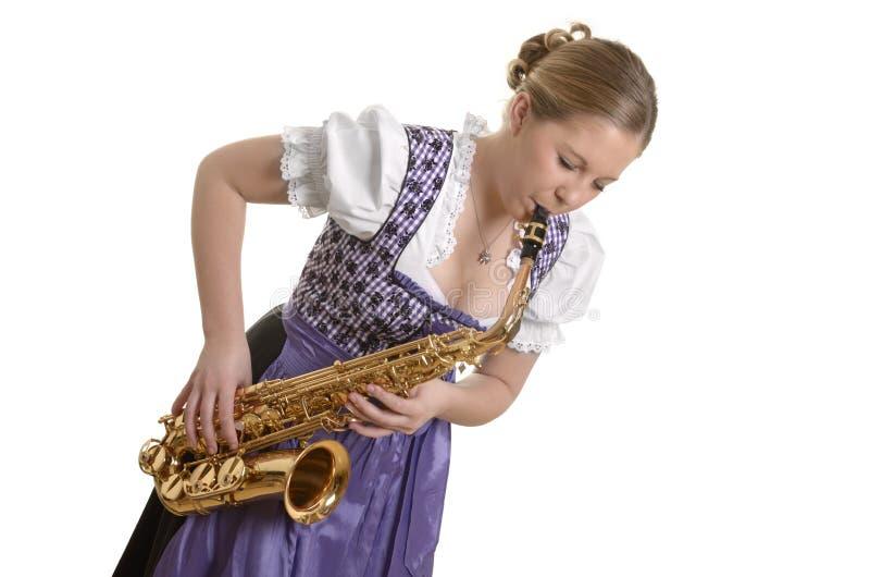 弹萨克斯管的少女装礼服的妇女 免版税库存照片