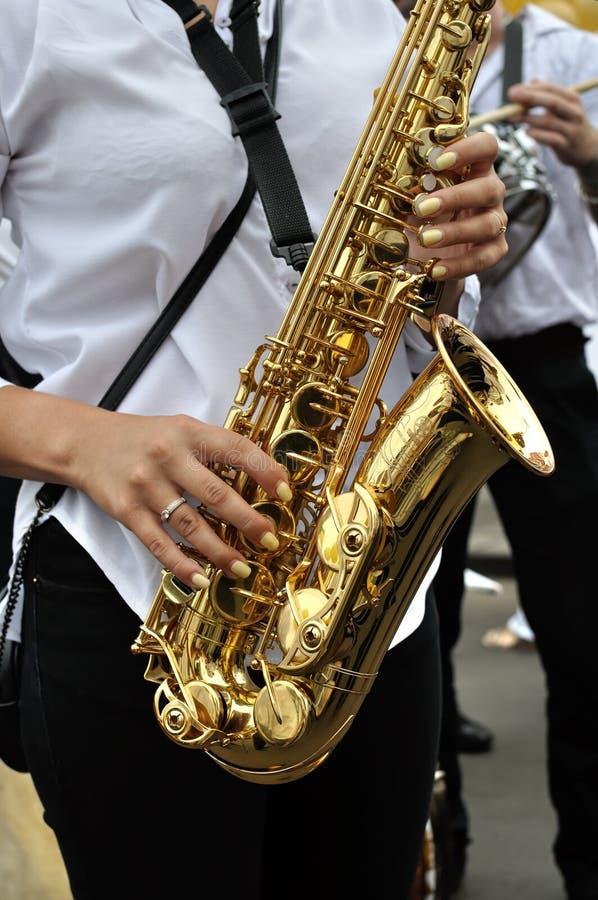 弹萨克斯管的无法认出的女性萨克斯管吹奏者 免版税库存照片