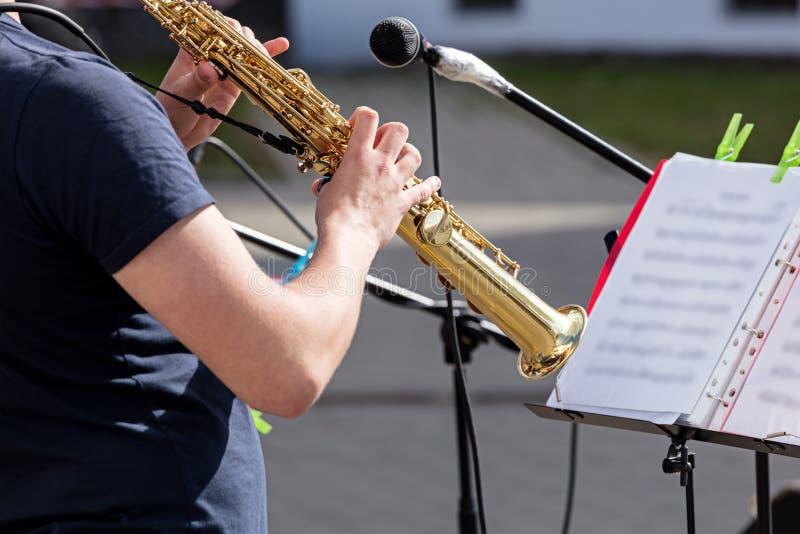 弹萨克斯管的男性音乐家的手 库存照片
