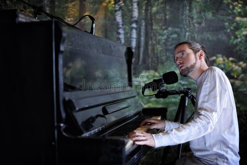 弹钢琴和唱歌在森林b的年轻英俊的有胡子的人 库存照片