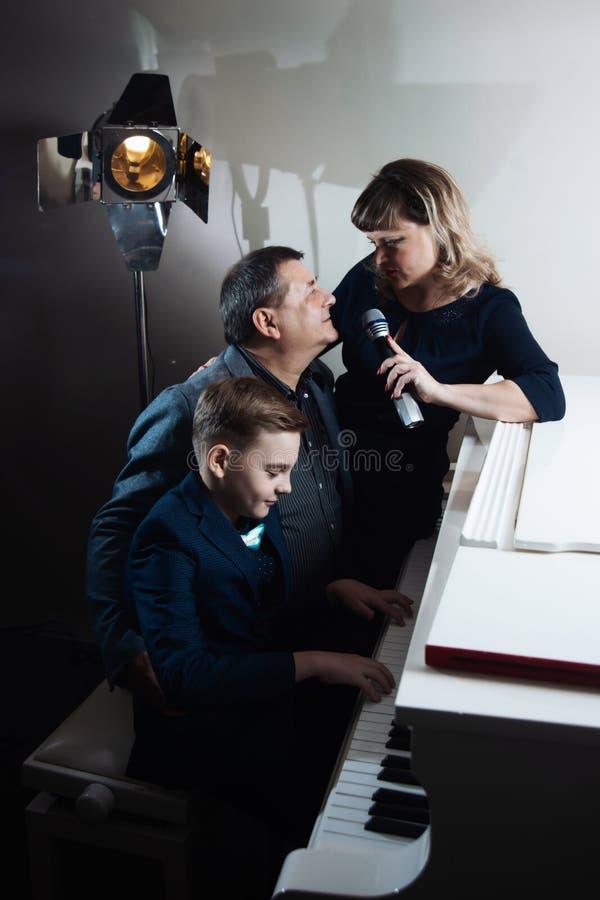 弹钢琴和唱歌曲的家庭入话筒 免版税库存图片