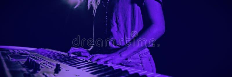 弹钢琴的女性音乐家的中间部分 免版税库存照片