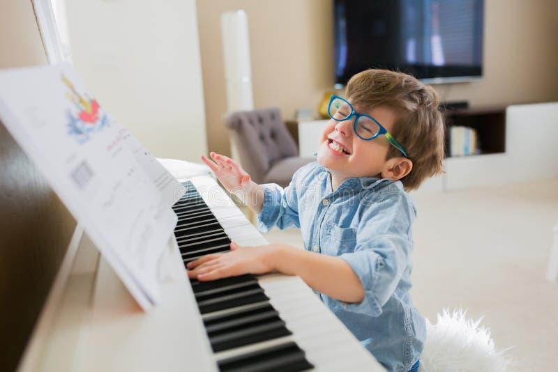 弹钢琴的快乐的小男孩 免版税库存照片
