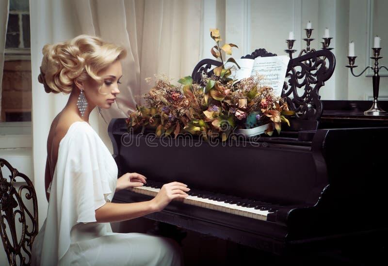 弹钢琴的美丽的年轻新娘 图库摄影