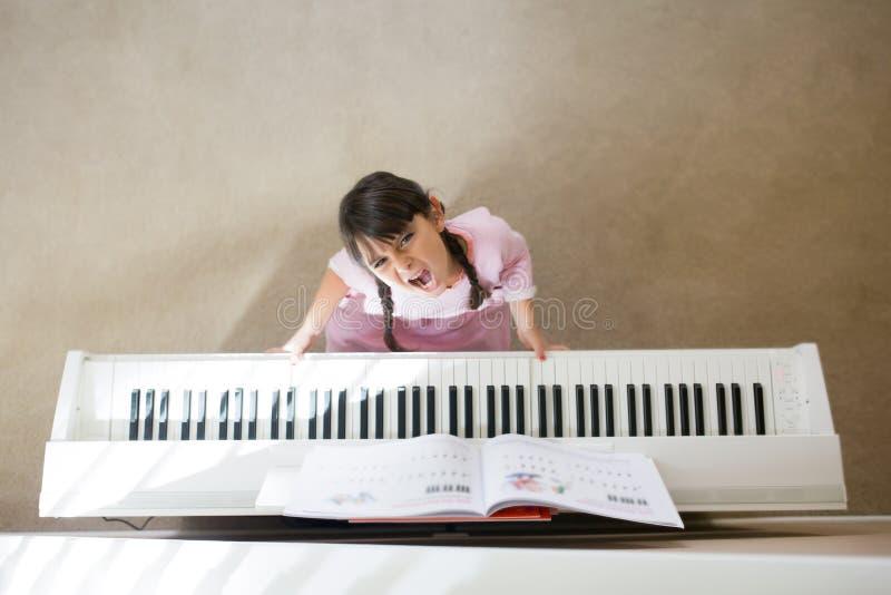 弹钢琴的被注重的女孩 免版税库存照片