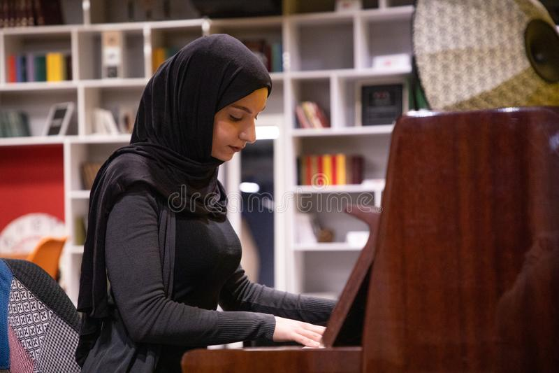 弹钢琴的hijab的可爱的回教女性 免版税库存图片