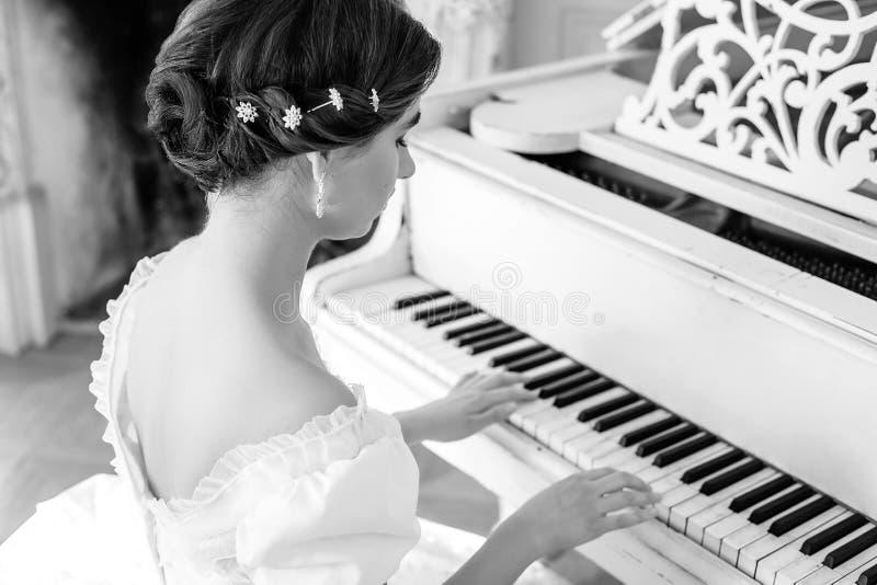 弹钢琴,在内部的一件美丽的礼服的美丽的女孩 库存图片