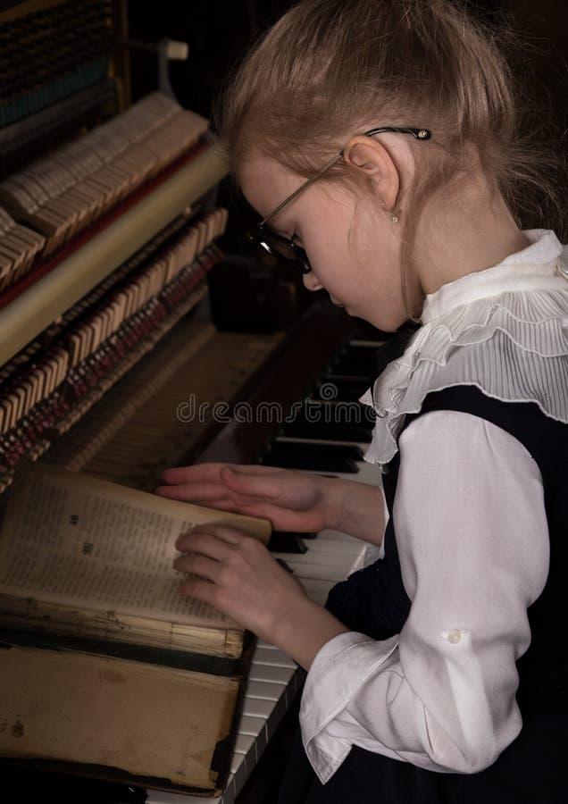 弹钢琴,孩子的一块大玻璃的严密的女孩仿效老师 图库摄影