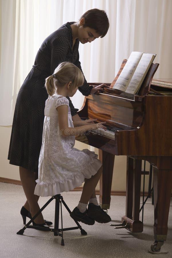 弹钢琴的女孩和老师 图库摄影