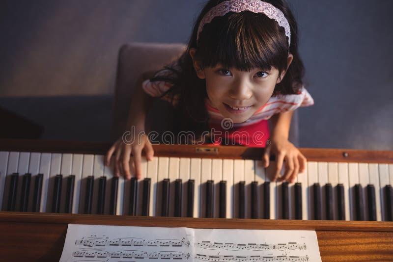 弹钢琴的女孩顶上的画象在教室 免版税库存照片