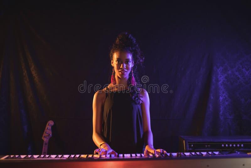 弹钢琴的女性音乐家在流行音乐音乐会 图库摄影
