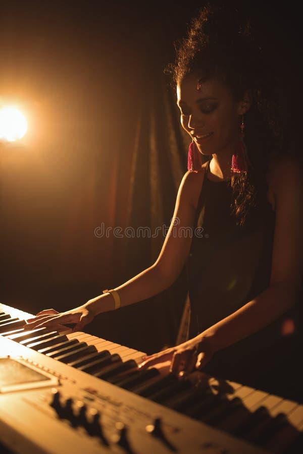 弹钢琴的女性音乐家在音乐音乐会 库存照片