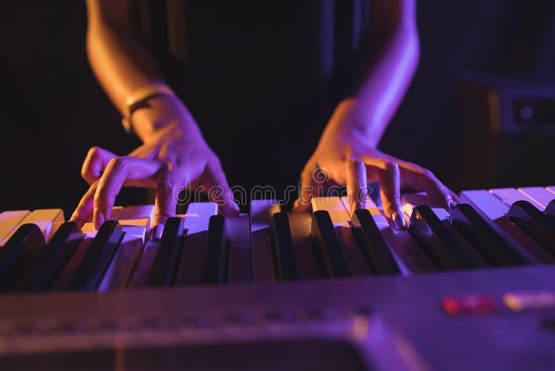 弹钢琴的女性音乐家的中间部分 库存图片