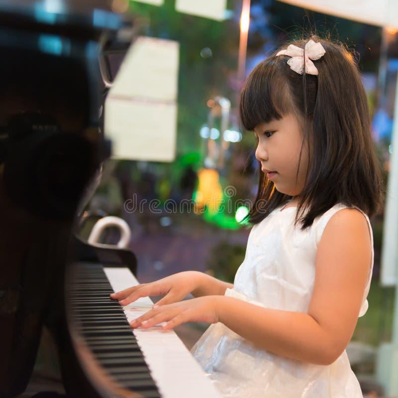 弹钢琴的小亚裔女孩 免版税库存照片