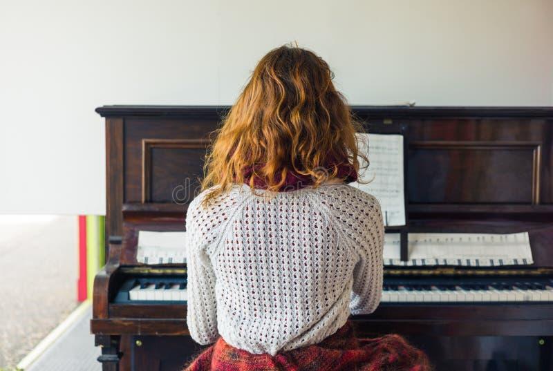 弹钢琴的少妇 免版税库存图片