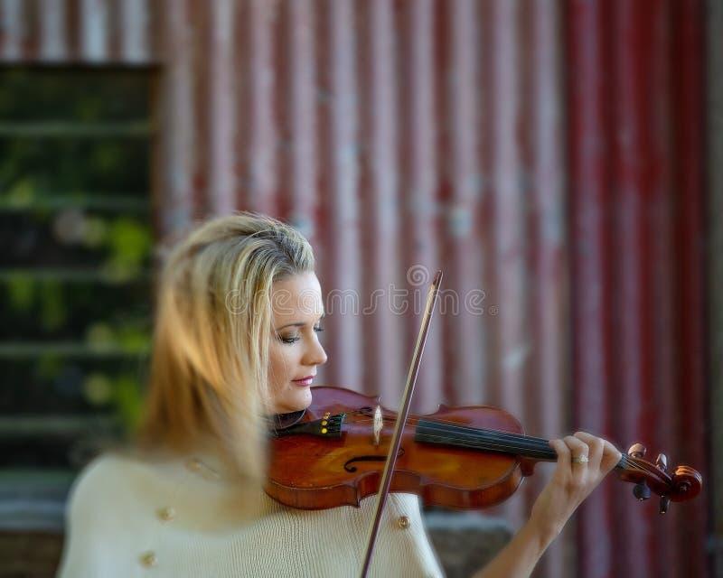 弹1893法国古色古香的小提琴的女性音乐家 免版税库存图片