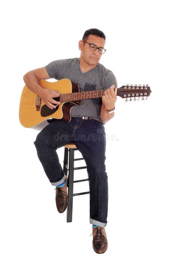 弹他的吉他的中年人 库存照片