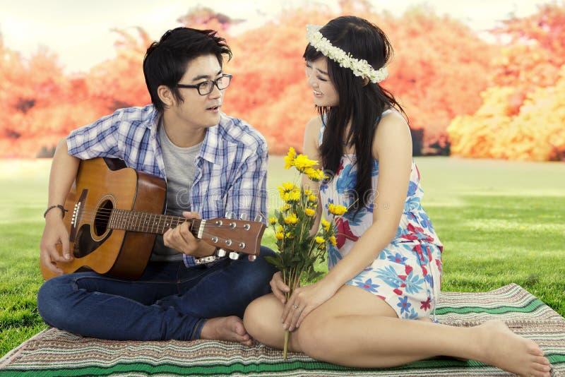 弹他的女朋友的年轻人吉他 免版税库存图片