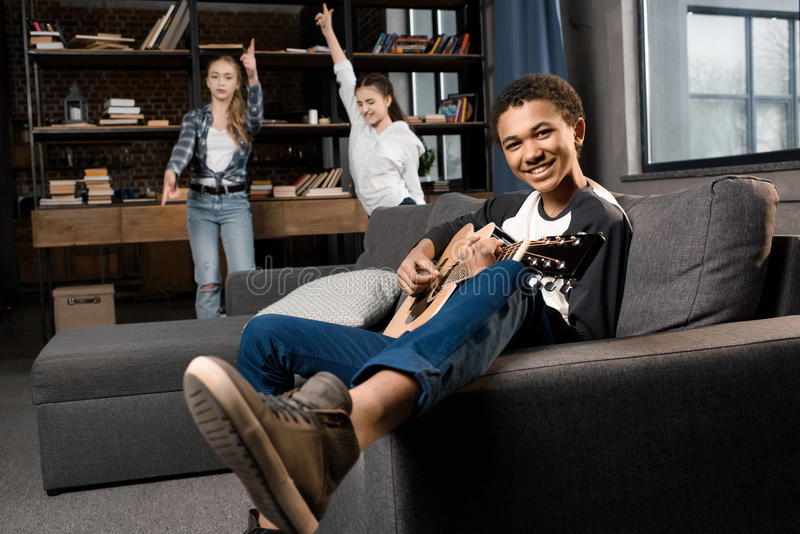 弹acustic吉他的非裔美国人的男孩,当在家时跳舞的女孩后边 免版税库存照片