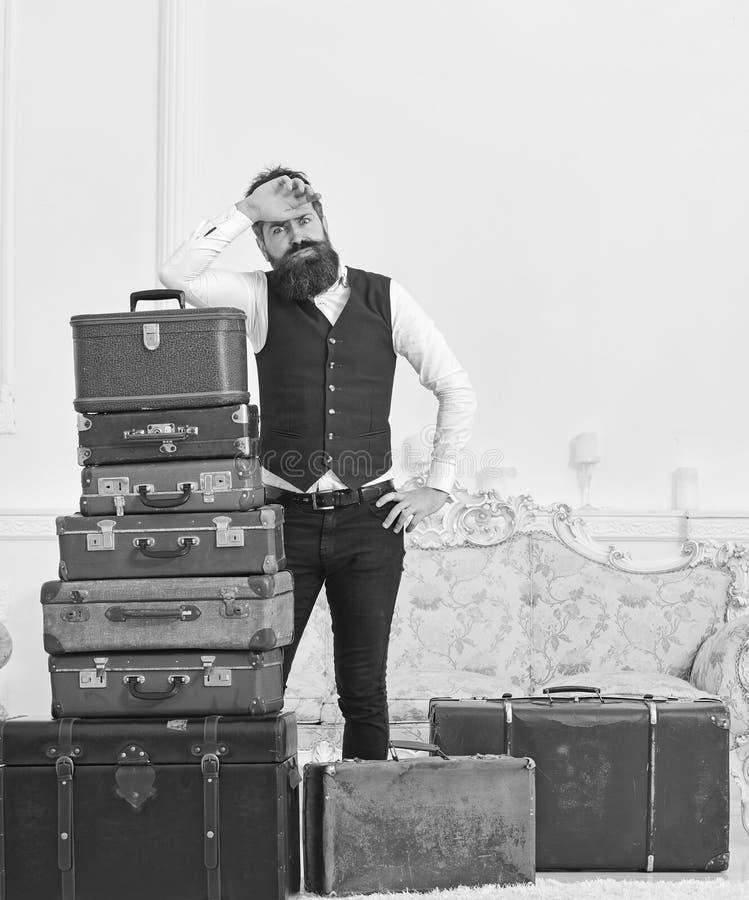 强壮男子典雅在疲乏的面孔,被用尽在包装结束时,在堆倾斜葡萄酒手提箱 行李和拆迁 库存照片