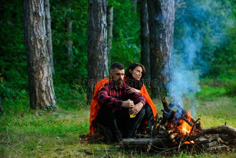 强壮男子用坐在篝火附近的啤酒,享受与妻子的假期 免版税图库摄影