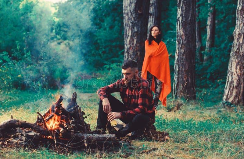 强壮男子用坐在篝火,与妻子的假期附近的啤酒 库存照片