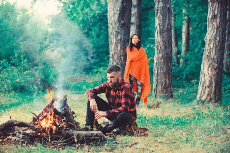 强壮男子用坐在篝火,与妻子的假期附近的啤酒 免版税库存照片