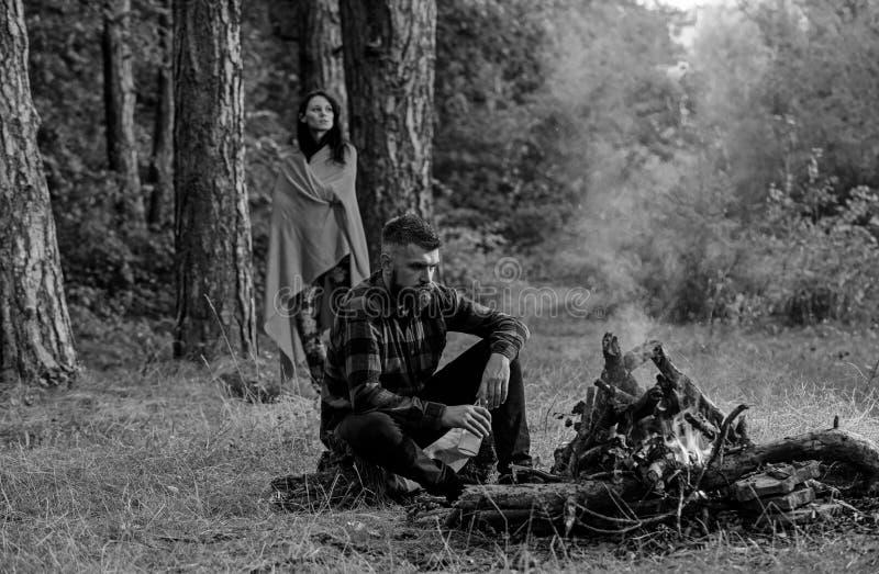 强壮男子用坐在篝火,与妻子的假期附近的啤酒 免版税库存图片