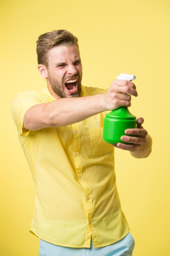 强壮男子的作为枪黄色背景的举行塑料浪花瓶 有喷水的人在手中假装射击攻击 免版税库存图片
