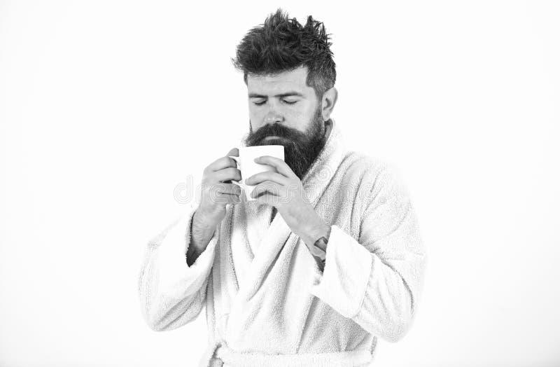 强壮男子的昏昏欲睡,困面孔在享受芳香的早晨喝咖啡 有胡子和被弄乱的头发的人在浴巾站立 库存图片