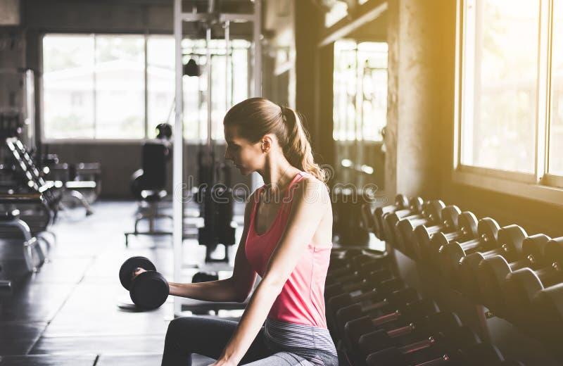 强女性解决与哑铃,运动服的妇女做锻炼在健身房 免版税图库摄影