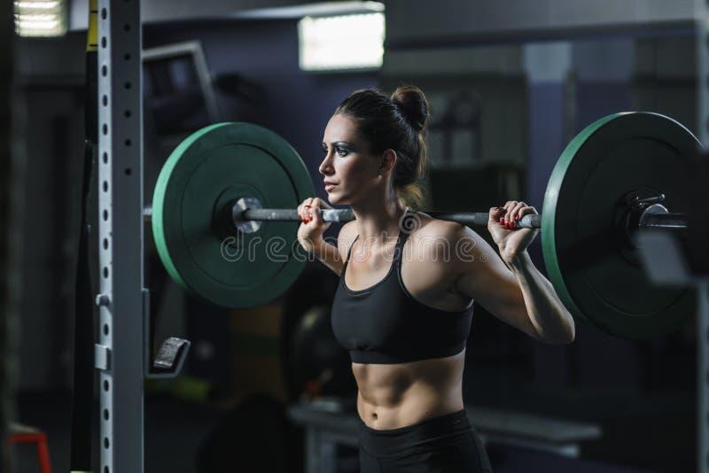 强有力的可爱的肌肉妇女CrossFit教练员做与杠铃的锻炼 免版税库存照片