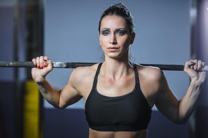 强有力的可爱的肌肉妇女CrossFit教练员做与杠铃的锻炼 图库摄影