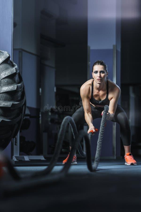 强有力的可爱的肌肉CrossFit教练员作战与绳索的锻炼 免版税图库摄影