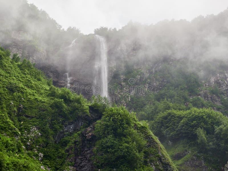 强有力的山射流下来从在浓雾的岩石 免版税库存照片