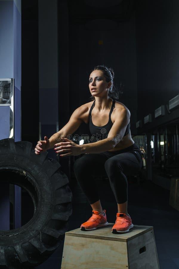 强有力的肌肉妇女CrossFit教练员跳在锻炼期间在健身房 库存图片