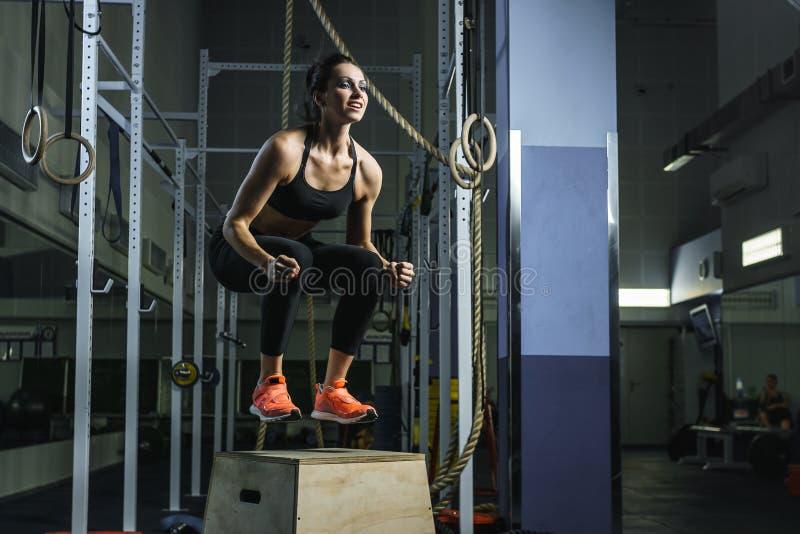 强有力的肌肉妇女CrossFit教练员跳在锻炼期间在健身房 库存照片
