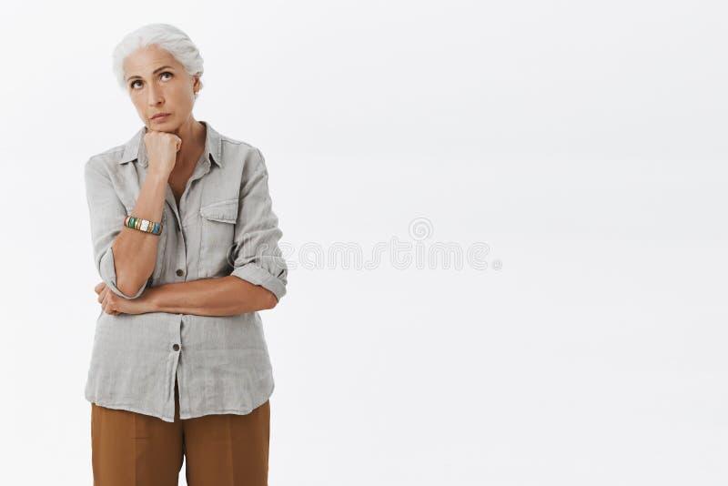 强烈的serious-looking关心的老妇人藏品拳头画象在查找的下巴上的站立在周道的姿势 免版税图库摄影