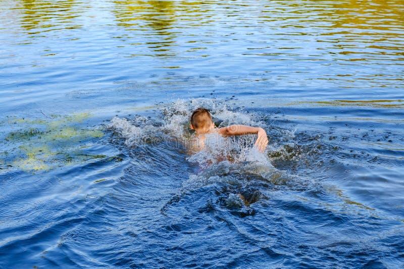 强的年轻人游泳在海 库存图片