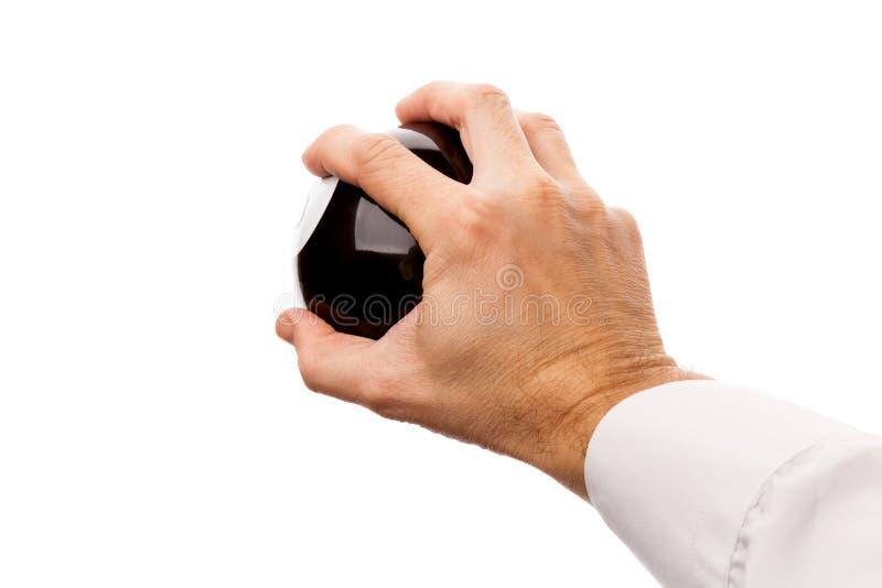 强的男性手拿着黑球形 免版税图库摄影