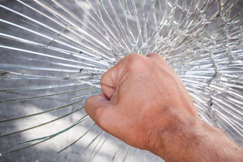强的男性拳头和残破的玻璃 免版税库存照片