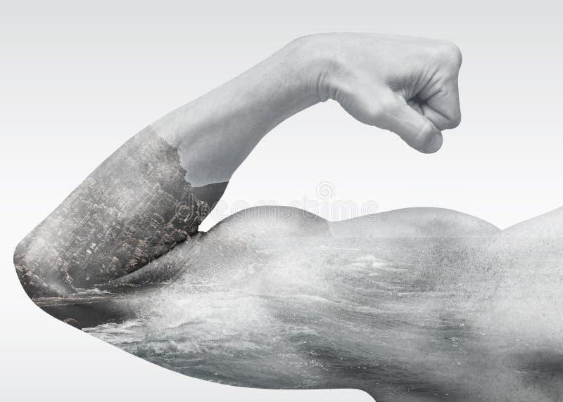 强的男性胳膊显示与沿海海风景的二头肌 免版税库存图片